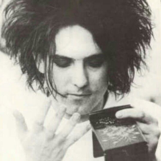 A young Robert Smith puts on his makeup